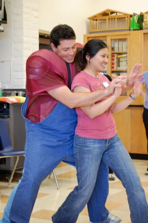 Ryan, instructeur en armure Fullpower, exerçant la position prête de dos avec une participante